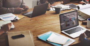 Bureau met mappen en laptops waar mensen werken